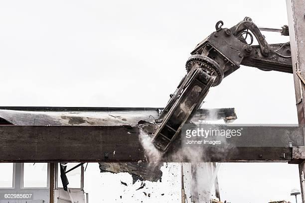 Digger demolishing building