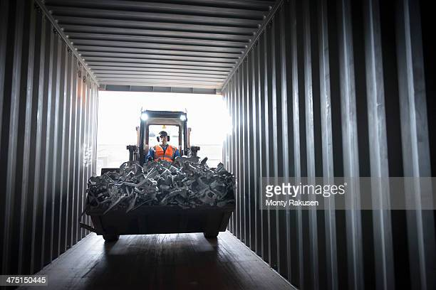 digger filling shipping container with scrap metal - scrap metal stock photos and pictures
