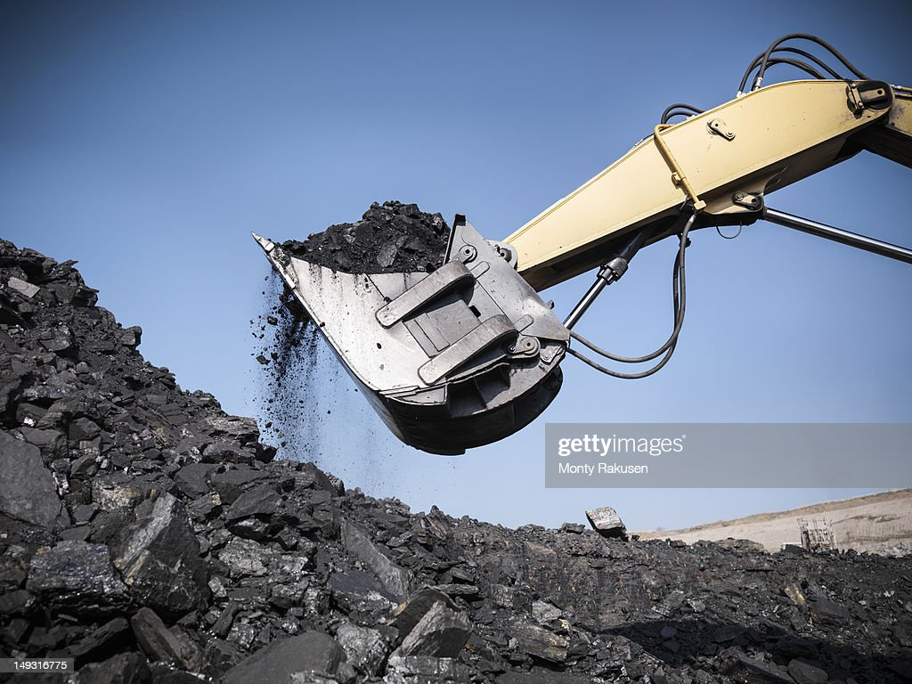 Digger lifting coal from opencast coalmine : Stock Photo