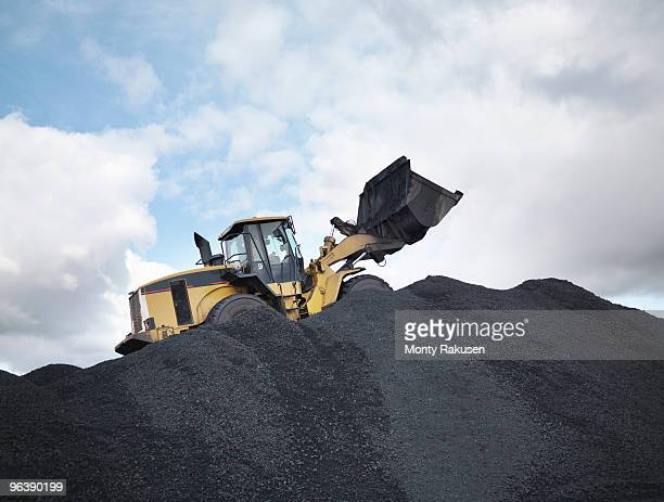 Digger On Pile Of Coal In Mine