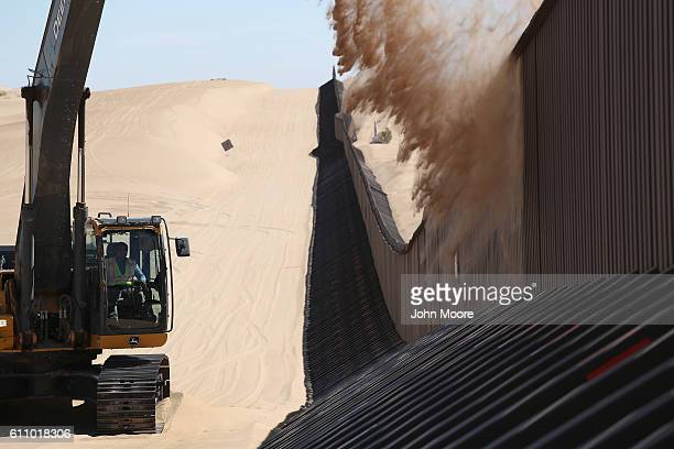 A digger removes sand drifts along the USMexico border fence on September 28 2016 in the Imperial Sand Dunes recreation center California Without...