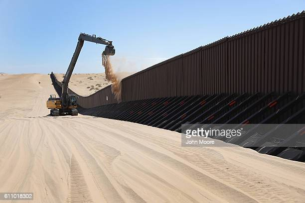 A digger removes sand drifts from the Mexican side of the USMexico border fence on September 28 2016 in the Imperial Sand Dunes recreation center...