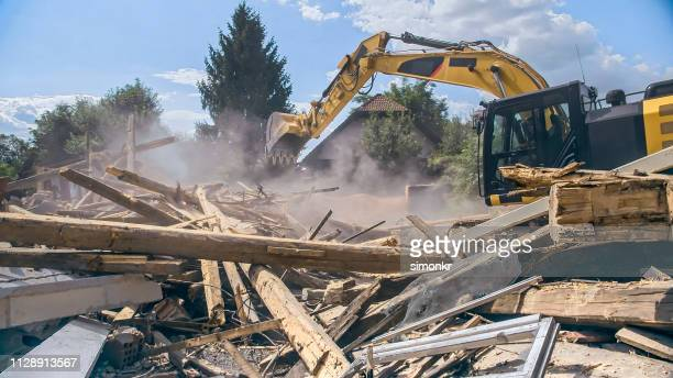 digger tipping over outer walls of building being demolished - demolishing stock pictures, royalty-free photos & images