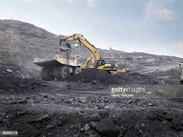 digger working in coal mine - coal mining stock photos and pictures