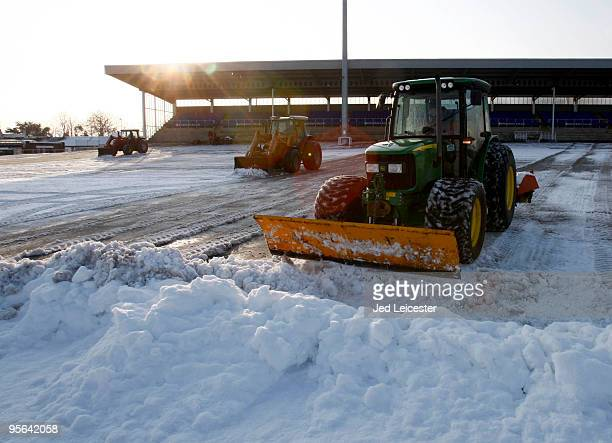 Diggers clear snow as winter race meetings at the Kempton Park race course are cancelled due to the snowy conditions on January 8 2010 in Sunbury...