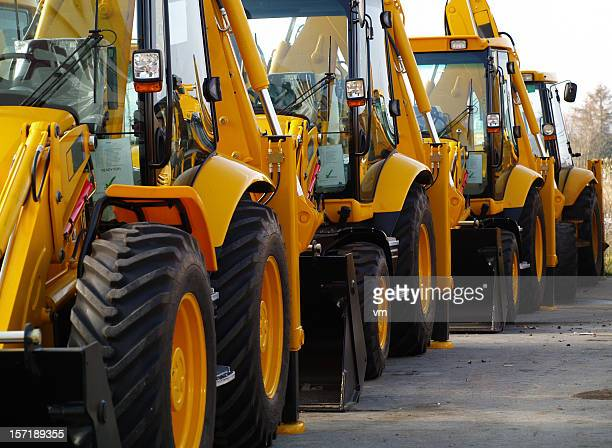 diggers in a row on industrial parking lot - excavator stock photos and pictures
