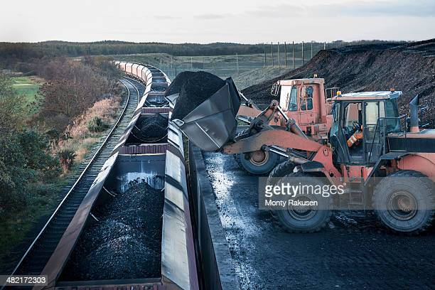diggers loading coal onto train at surface coal mine at dawn - coal mining stock photos and pictures