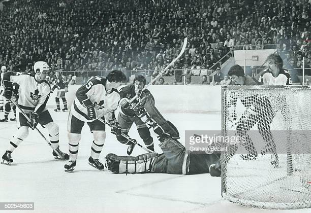 Digging Away Leafs' Pat Boutette digs the puck out from under sprawling New York goalie Dunc Wilson during Saturday night's NHL game at Maple Leaf...