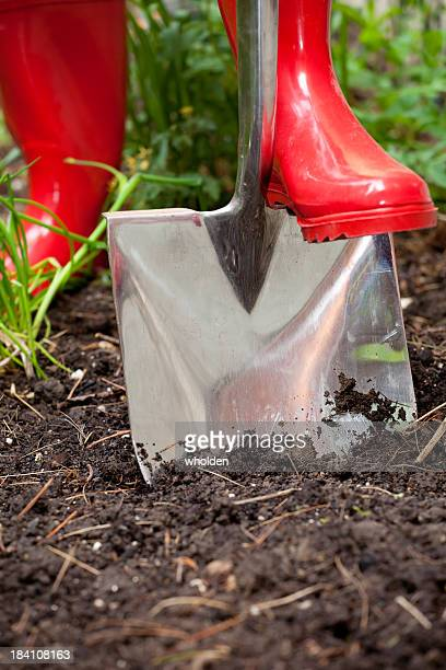 digging in red boots - red boot stock pictures, royalty-free photos & images