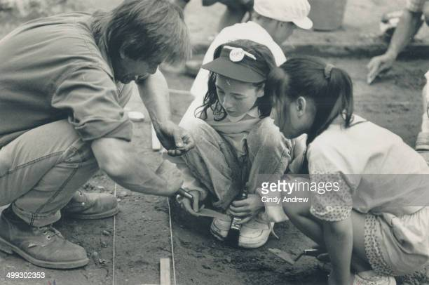 Digging in Teacher Ron Postill pitchs in with pupils in a dig at Leslieville Public school as archeologists stand by to identify their finds