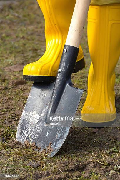 digging in yellow rubber boots - lutavia stock pictures, royalty-free photos & images