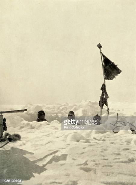 Digging to ascertain the depth of snow covering a depot left by the Discovery expedition', circa 1908, . Expedition members dig down to find supplies...