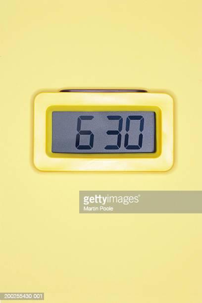 Digital alarm clock against yellow background