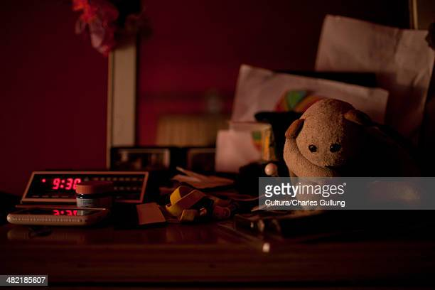 Digital alarm clock and toys on bedside table
