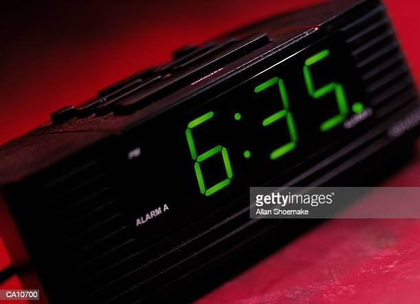 Digital alarm clock on red background, close-up, tilt