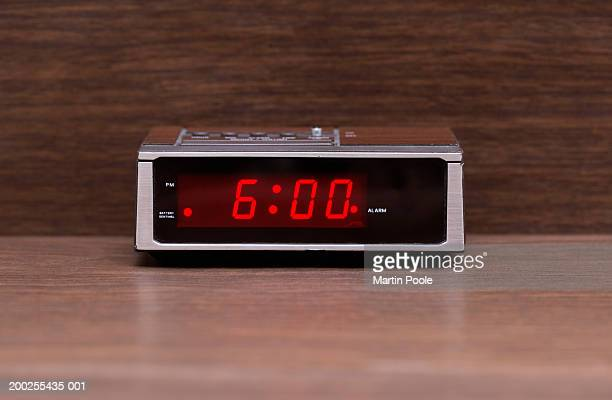 Digital alarm clock on wooden surface