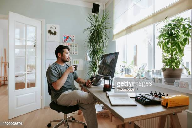 digital artist contemplates during coffee break in his home office - tracksuit bottoms stock pictures, royalty-free photos & images