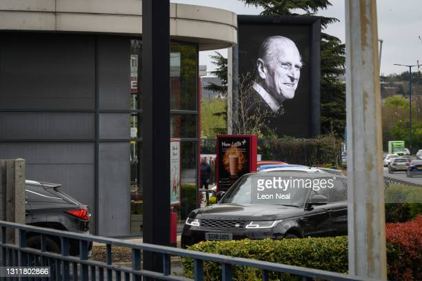 Digital billboard displays a portrait of Prince Philip, Duke Of Edinburgh who died at age 99, as cars queue at a drive-thru coffee shop on April 10,...