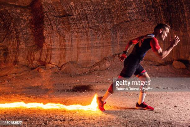 digital composite image of athlete running in front of fire - cave fire stock photos and pictures
