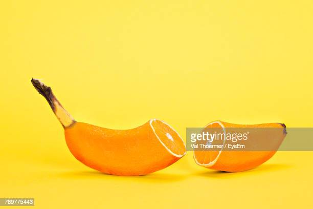 Digital Composite Image Of Banana And Orange Against Yellow Background