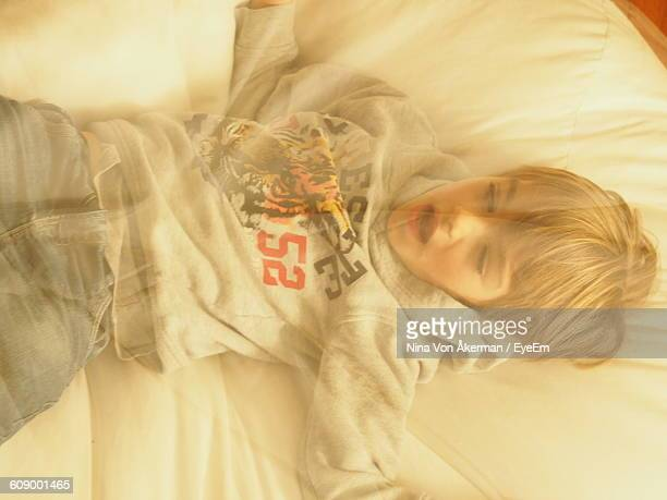 Digital Composite Image Of Boy Relaxing Below Mosquito Netting On Bed At Home