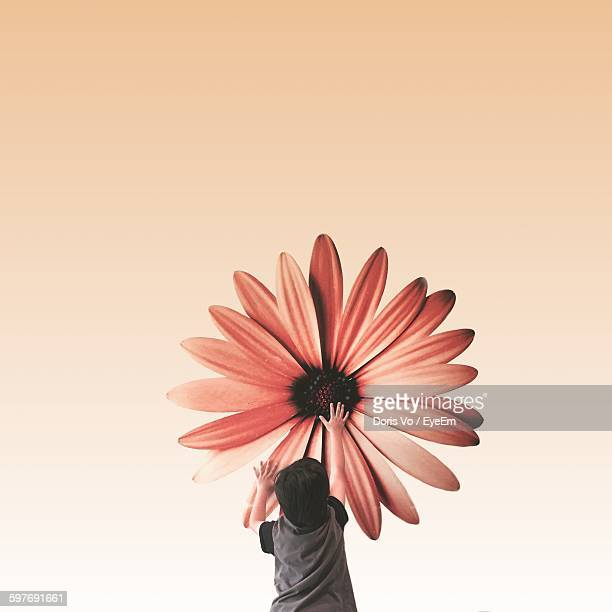 Digital Composite Image Of Boy Touching Flower Against Yellow Background