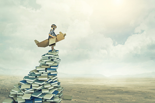 Digital Composite Image Of Boy With Wings Standing On Stack Of Books At Landscape Against Sky - gettyimageskorea