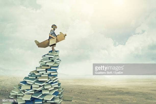 digital composite image of boy with wings standing on stack of books at landscape against sky - erwartung stock-fotos und bilder