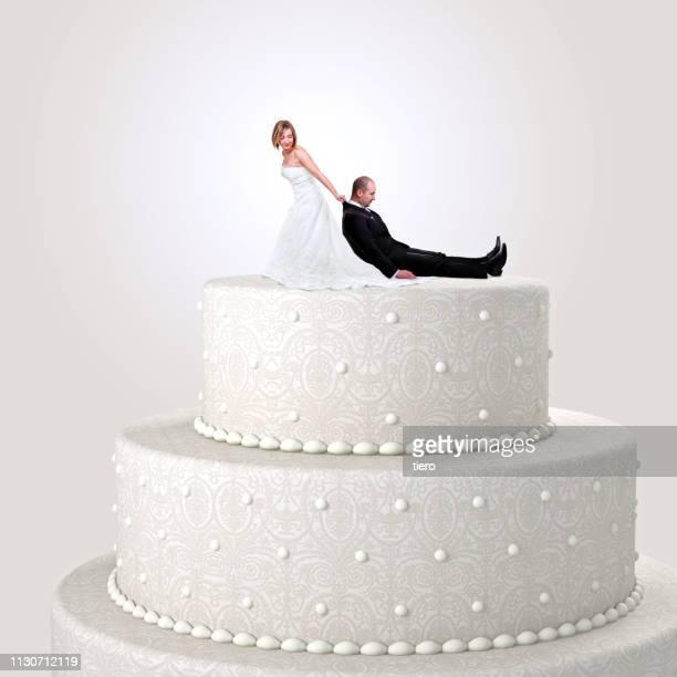 digital composite image of bride pulling bridegroom on wedding cake against white background - wedding cake figurine stock pictures, royalty-free photos & images