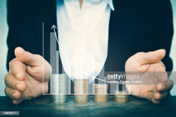 digital composite image of businessman cupping hands around coins stack and bar graph - business plan stock pictures, royalty-free photos & images