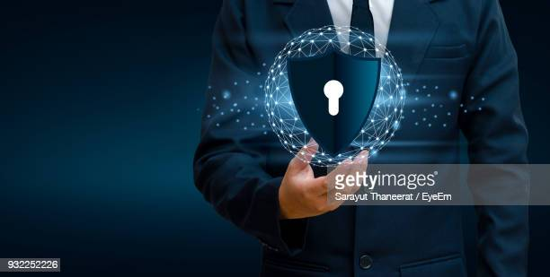 Digital Composite Image Of Businessman Holding Computer Icon While Standing Against Colored Background