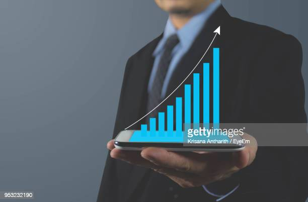 Digital Composite Image Of Businessman Holding Mobile Phone With Bar Graph On Screen