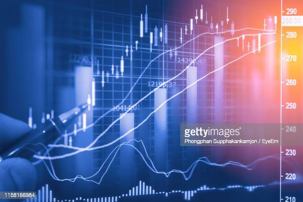 digital composite image of businessman holding pen against stock market data - bar graph stock pictures, royalty-free photos & images
