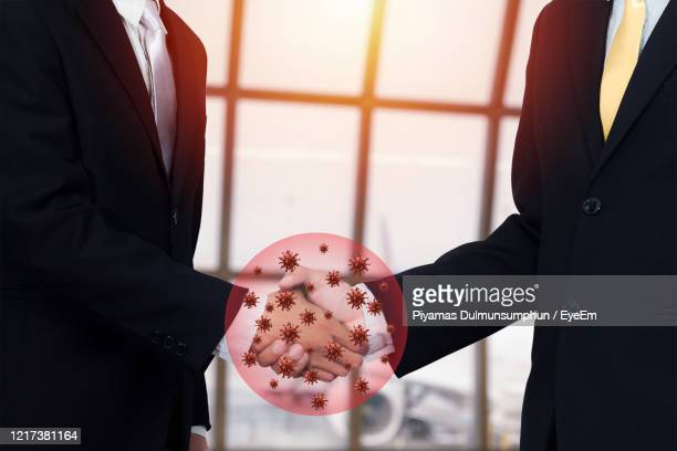 digital composite image of businessman shaking hands with icons in office - pathogen transmission stock pictures, royalty-free photos & images