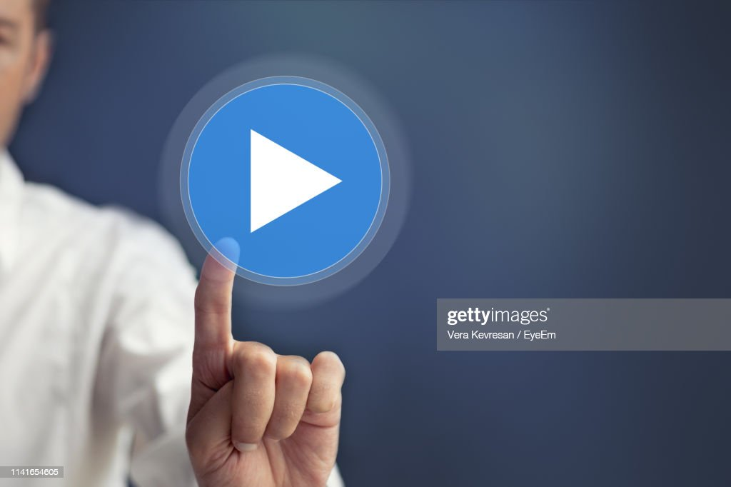 Digital Composite Image Of Businessman Touching Play Button Against Blue Background : Stock Photo