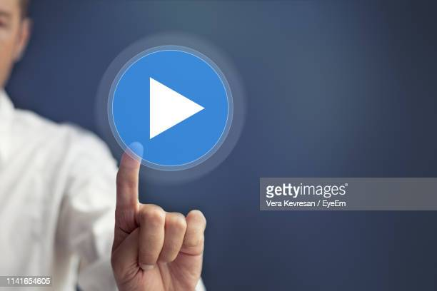 digital composite image of businessman touching play button against blue background - play button stock photos and pictures