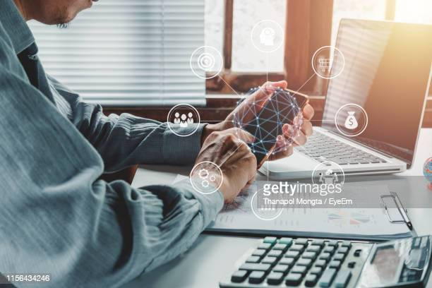 digital composite image of businessman using mobile phone on desk in office - digital composite stock pictures, royalty-free photos & images