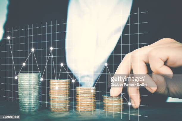 Digital Composite Image Of Businesswoman With Coins Stack And Graphs On Inter Display