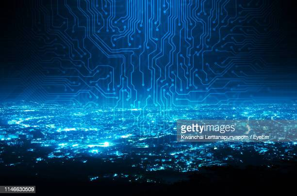 digital composite image of circuit board over illuminated cityscape at night - circuit board stock pictures, royalty-free photos & images