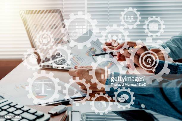 digital composite image of coworkers discussing data on desk in office - cog stock pictures, royalty-free photos & images