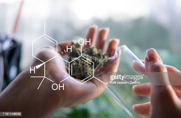 digital composite image of cropped hands holding container and marijuana joint by molecular structure - physical structure stock pictures, royalty-free photos & images
