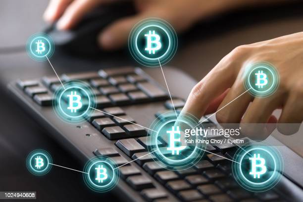 digital composite image of cropped hands using computer keyboard by bitcoin icons - bitcoin stock pictures, royalty-free photos & images