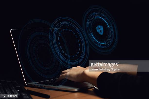 digital composite image of cropped hands using laptop against black background - deep learning stock pictures, royalty-free photos & images