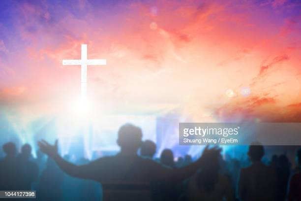 digital composite image of crowd and cross against cloudy sky during sunset - god stock pictures, royalty-free photos & images