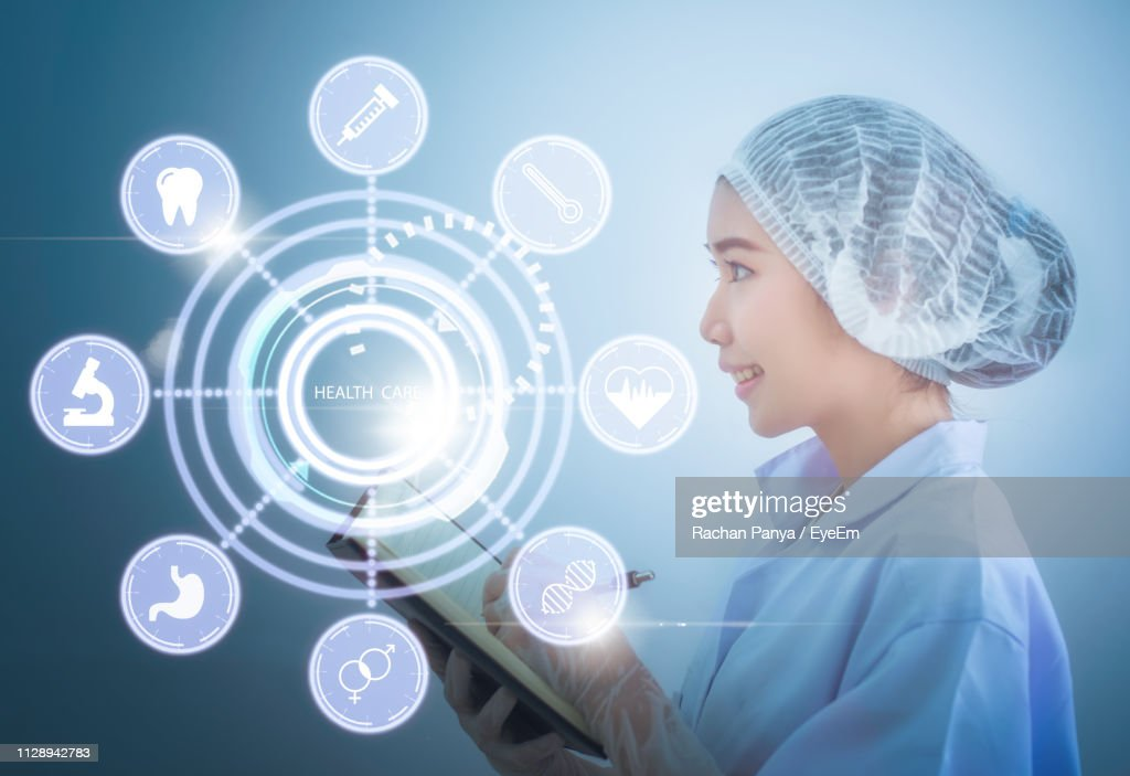 Digital Composite Image Of Doctor Writing With Medical Icons While Standing Against Blue Background : Stock Photo