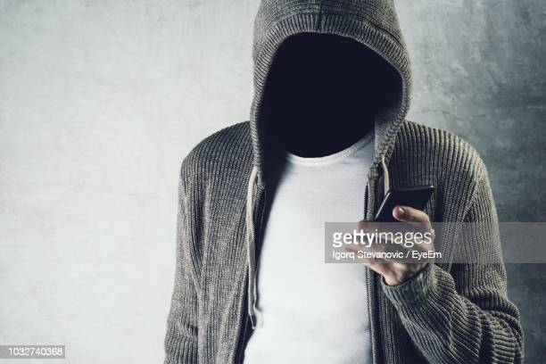digital composite image of faceless man using smart phone against wall - unrecognizable person stock pictures, royalty-free photos & images