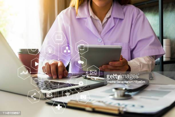 digital composite image of female doctor using laptop and digital tablet with various signs in foreground - medical icons stock pictures, royalty-free photos & images