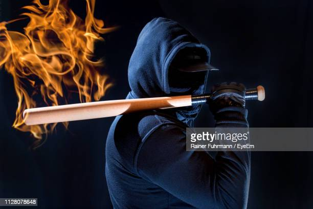 digital composite image of fire by man holding bat against black background - in flames i the mask stock pictures, royalty-free photos & images
