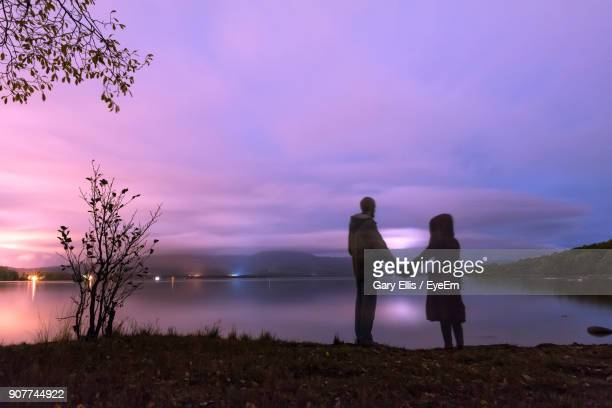 Digital Composite Image Of Friends Standing Against Lake During Sunset