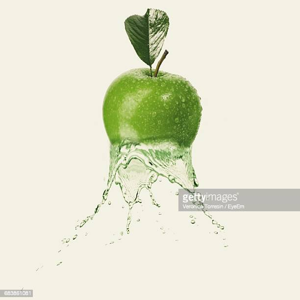 Digital Composite Image Of Granny Smith Apple And Water Against White Background